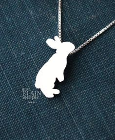 """This tiny Rabbit necklace is a perfectly delicate way to showcase your love of all things huggable! Just ⅝"""" at its largest dimension, our pendants are made by hand with love. This pendant is cut, soldered, finished, and polished completely by hand. It comes with our beautifully"""