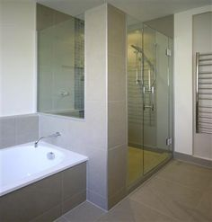Idea for bathroom- bath, tiles and towel rail.