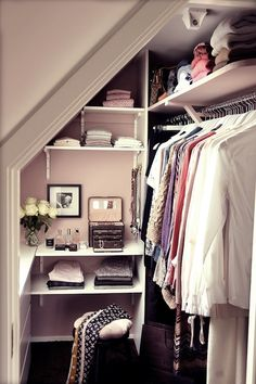 teen closet - pink closet walls, walk in closet, built in vanity, black stool, built-in shelves, sloped ceiling