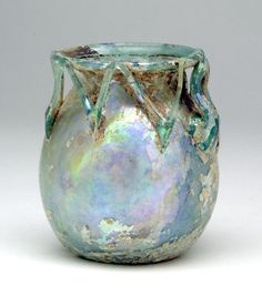 "Ornate Jar with Trailed Decoration and Fine Iridescence. Roman, 4th to 5th century AD. Height: 2-7/8"". Blown from aqua-green glass.  $2,473"