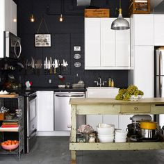 love those dark walls and the contrast of the island with the more modern elements of the kitchen.