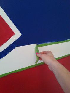 Muralist, Adrienne, peels the tape off a Montreal Canadiens hockey mural