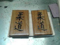 Judo in het Japans in eikenhout gesneden