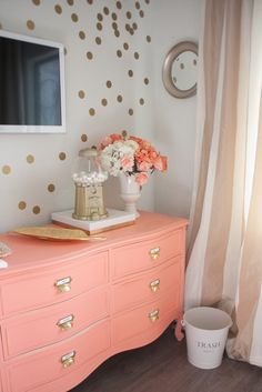 Coral dresser with gold handles & oversized gold accent confetti on the wall