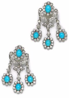 A pair of turquoise and diamond chandelier earrings featuring oval-shaped turquoise cabochons, each within a diamond surround, suspended from diamond accented decorative work; estimated total diamond weight: 4.00 carats; mounted in eighteen karat white gold; length: 2in.