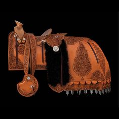 Saddle, Spanish-style~John Willemsma partnered with Scott Hardy and Russell Yates in a tribute to Mexican craftsmen who built remarkable saddlery for their patrons. The entire saddle is adorned with hand-carved and filigreed leather sewn to a dyed background panel. Each panel is separately appliquéd onto the skirting. The black Angora goat drops and the anquera, or rear skirting, give the saddle a regal presence.