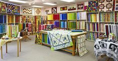 Michèle Santerre, one of two owners of The Running Stitch in Kanata, Ontario, loves color, which is reflected in a vast selection of prints. An 8-foot-long wall of fat quarters is a favorite of customers. While they shop, customers lay out fabric samples and patterns on a table in the middle of the room.
