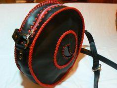 Bolso en piel de color negro , detalle de piedra en forma de cuerno, todo cosido a mano con tireta de cuero en rojo, cierre de cremallera.