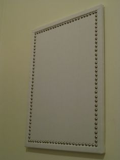 Regular cork board covered in fabric with upholstery tacks... totally bril!