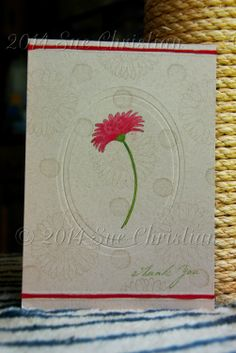 I stamped with Versamark ink first, then embossed with an Oval Nestabilities die & stamped the flower with StazOn ink & coloured it with Derwent  Inktense pencils. I embossed two straight lines at the top & bottom of the card, just wide enough to hold a 6 strand piece of embroidery floss, & glued in my floss.