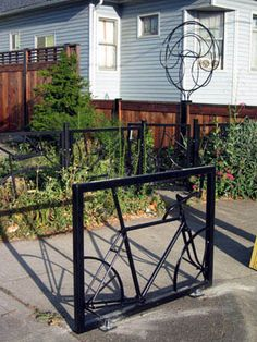 Small World Cafe  by Matt Cartwright, Portland, OR  A bike rack that uses an old bicycle welded into a rectangular frame and powder coated. The rack is bolted to a sidewalk near N. Sumner and Albina. The globe sculpture in the background is to draw attention to the Small World Cafe. www.cartwrightdesigns.com