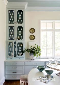 X-motifs on the island base and on glass-front cabinets are echoed by the design of custom bar stools.- Photo: Nancy Nolan / Design: Kimberly Harper