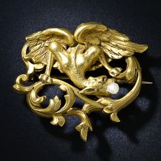 A sinewy Griffin, holding a freshwater pearl in his beak, is poised and ready to pounce in this finely sculpted mythological pin with a warm velvety patina from fin de siecle France. 1 1/2 inches by 1 3/8 inches.