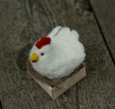Start your own chicken farm! This listing is for one (1) needle felted laying hen. Origami box (made with a nicely textured oatmeal paper) measures about 2 inches square, and hen sits comfortable in a soft nest of wool. Look carefully and youll find one small egg (carefully made from Sculpey). Eyes are made using small black glass beads, securely attached with heavy-duty thread. Buy one, or collect a whole flock. Turn your desktop into a coop. Nesting hens will vary slightly (I call it…