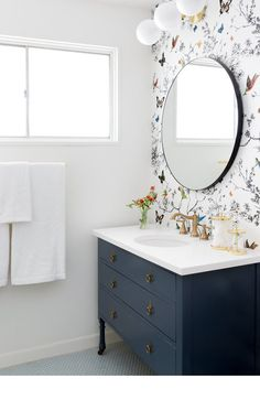 Colourful powder room with floral-inspired wallpaper and blue vanity