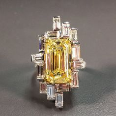 Art Deco 8.75 carats Emerald Cut Fancy Yellow diamond ring with 4+ carats baguette white diamonds. Very unusually and attractive setting