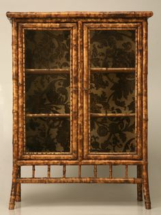 Antique bamboo vitrine with tooled leather interior, fabric interior.