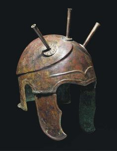 A CHALCIDIAN TYPE BRONZE HELMET  4TH CENTURY B.C.  The crown with carinated perimeter extending into triangular contour above the brow, three plume holders attached above, contoured 'eyebrow' at centre-front, with hinged cheekpieces, repaired 12 3/8 in. (31.5 cm.) high incl. plume holders