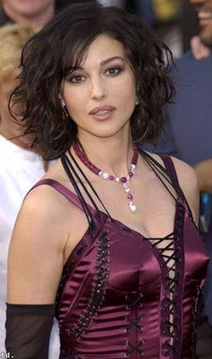 Google Image Result for http://www.curly-hair-styles-magazine.com/images/curly-hair-cut-medium-length-09.jpg.  celebrity Monica Bellucci has medium to long, curly hair in a tousled, side-parted style with a fringe, or bangs. Her hair color is dark brown.