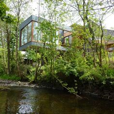 This house cantilevered over a river in Wales is by London studio Featherstone Young.
