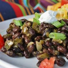 "Black Beans | ""Black beans cooked with onion, green pepper and garlic, seasoned with bay leaves, salt, cumin, and oregano. White wine and vinegar give these beans a nice little bite."""
