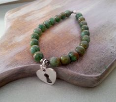 Bracelet made of wonderful glass beads in green and brown colors, silver plated and gunmetal elements. Silver plated heart-padlock pendant. Free gift box. A great idea for a gift for her.