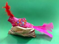 paper mâché birds made using a paper plate folded in half, stuffed with newspaper for body and a cardboard triangle for a beak. The nest is a scrunched paper bag.