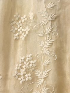 1834 wedding dress detail consisting of a pelisse robe with large imbecile sleeves and bell shaped skirt. It is made of white muslin with self coloured cotton embroidery in a formal floral pattern. There is a bow of satin at ankle height, in the front of the skirt. The dress is lined with silk and fastens at the neck and waist with black metal hooks and eyes. There is an additional silk tying ribbon inside the waist.