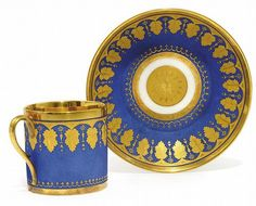 A MATT-BLUE AND GILT COFFEE-CUP AND SAUCER <br />EARLY 19TH CENTURY, INCISED V MARK, PERHAPS RUSSIAN <br />Decorated in the Empire style with a band of tooled matt-gilt leaves alternating with pendant drops below a gilt band, the interior of the cup richly-gilt, the saucer with a flowerhead medallion (2)<br />