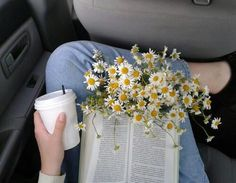#Girl with drink and daisies reading a book.