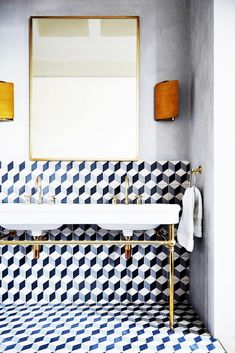 Tiled flooring, large mirror, white sink with gold accents, grey walls, wooden lamps