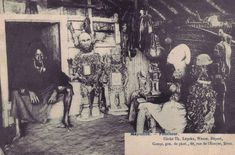"""""""showing a collector of African art specialized in Kongo nkisi nkondi smoking a pipe in his living room. :-) I count four big statues, two smaller in the corner and a dog on the ground in front of them. On the right, there also appears to be hanging a zoomporphic figure on the wall. I have never see so many figures together owned by a single diviner. """""""