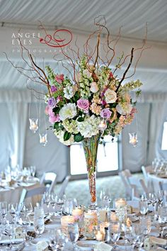 Elevated centerpieces arranged with pastel roses, light pink and white hydrangeas, pastel colored stock accented with curly willow. Image by Angel Eyes Photography. Designed by Phillip's Flowers.
