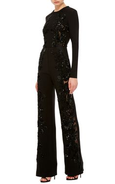 This long sleeve **Elie Saab** jumpsuit is rendered in crepe cady and features a jewel neckline with a beaded embellishment along the front and a fluid straight leg pant.
