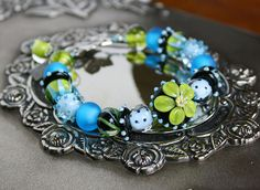 Blue Bayou is a stunning artisan bracelet made by me featuring a stellar set of my own handmade lampwork beads in watery shades of teal and aqua with black and seaweed green. The focal point for this amazing bracelet is a button shaped glass bead with a large, murrini centered flower on either side. accompanied by lots of interesting round beads of varying designs and intervals of disc beads that spin freely over silver lined seed beads for just a hint of sparkle. The closure is a large…