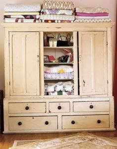 An antique cupboard displays the homeowner's collections of quilts, pocketbooks, and more.