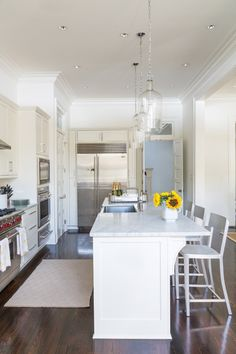 Carrera marble counters, stainless steel and white cabinets provide a cool contrast to the warmth of the reclaimed pine floors. Ellen purchased the glass pendant fixtures above the island online from Shades of Light.