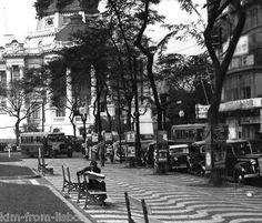 Praça Floriano  Vendo a tranquilidade com que o senhor, sentado num banco, lê o jornal, não posso deixar de lamentar em que se transformou o Centro do Rio nos dias de hoje.