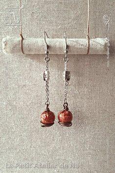 """Réalisation [ Fait-Main ] avec du fil aluminium anodisé Marron Chocolat Mat, une chaîne, des anneaux et des crochets d'oreille en acier inox, une perle métallique dite """"tibétaine"""". Chaque pendentif de boucle d'oreille est fait d'une perle de résine dont le mélange, préparé à la main avec soin, est composé de pigments et de micas. L'aspect souhaité : un rendu telle une nébuleuse profonde, dense, intense, cuivrée et scintillante."""
