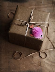 Here's a fun idea: Use a small honeycomb party decoration & fold half open onto a gift wrapped in brown paper / http://mokkasin.blogspot.ca/2013/01/multifunktion-i-en-liten-pappersfigur.html#