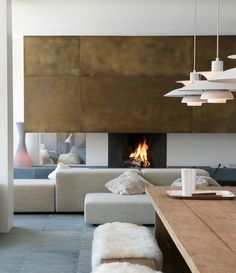 Living Room - Clever styling with brass paneling above fireplace....those white pendant light fixtures, excellent choice!