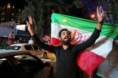 An Iranian man flashes the victory sign as an other holds the Iranian national flag during celebration in northern Tehran on July 14, 2015,after Iran's nuclear negotiating team struck a deal with world powers in Vienna. Major powers clinched a historic deal Tuesday aimed at ensuring Iran does not obtain the nuclear bomb, opening up Tehran's stricken economy and potentially ending decades of bad blood with the West.