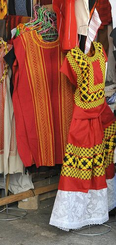 Mexican Clothing Oaxaca    Clothing from Oaxaca displayed in a shop in the city of Oaxaca, Mexico. The red and yellow huipil and skirt is from Juchitan, a large Zapotec town in the Isthmus of Tehuantepec. The long red and yellow huipil at left is probably from the Mixe community of San Juan Guichicovi, also in the Isthmus.