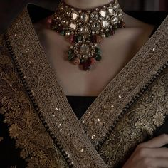 Black Benarasi saree accessorised with a stunning uncut diamond necklace. The necklace is strung together with emeralds, tourmalines,…