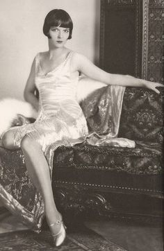 STUDIO PORTRAIT – MOVIE STAR – LOUISE BROOKS – SITTING ON SOFA WITH ARM RESTING ON BACK IN SATINY DRESS WITH FLAPPERSPANGLES