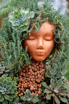 Beautiful garden art. (Could this be made with a spray painted styrofoam head as a cheap alternative?)