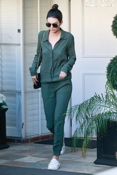 Kendall Jenner wearing Fendi Pompom Bag Charm, Saint Laurent Monogramme Small Suede Cassandre Bag and MONROW Crepe Long Sleeve Jumpsuit in Camo