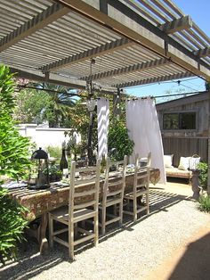 Pretty outdoor dining room - love the pergola framework - and I love the idea of the curtains for privacy.