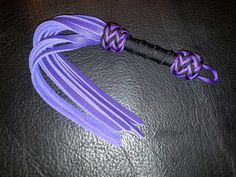 "Pocket/intimate flogger in purple bullhide. 16, 13""x3/8"" falls. Acid purple and black paracord wrap and knots. This one is a little longer than most of my pocket floggers. Super supple hullhide, in bright purple."