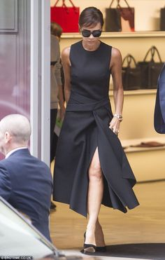 New hair, do care: Victoria Beckham debuted a chic new side fringe as she flashed her slim legs in a thigh-split black dress from her own collection on a shopping trip in London on Sunday